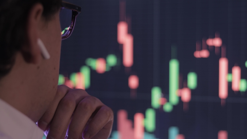Businessman analyzing a graphic of a stock exchange chart. Back of the head of a young male businessman looking at a stock diagram on the big screen of the computer Royalty-Free Stock Footage #1054702004