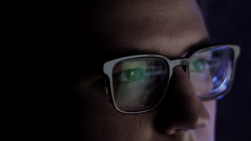 Man in eyeglasses late at night scrolling in front of laptop. Coder, programmer or developer using laptop in dark. Close up of glasses with reflection of computer screen.