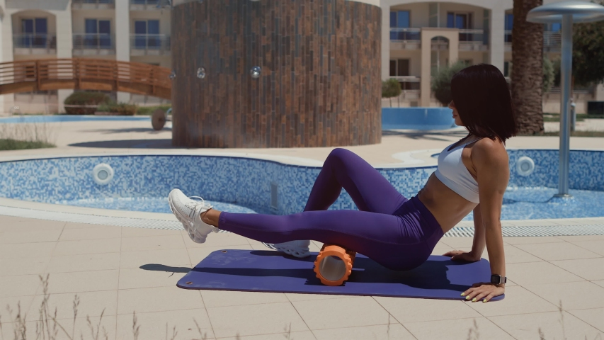 Sporty woman stretching and fitness massage with foam roller. Athletic female massaging legs on yoga mat with foam roller outdoors.
