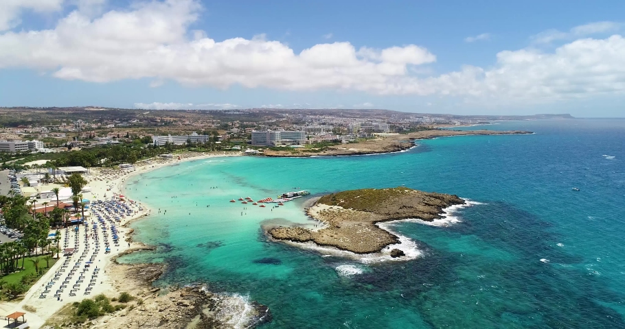 Aerial footage view of turquoise transparent crystal clean water of Nissi beach, Ayia Napa, Famagusta, Cyprus from above on a windy day.