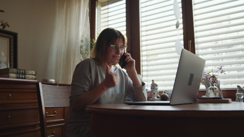 Portrait of an adult joyful woman talking on the phone and working on a laptop showing the YES sign. Mature happy woman freelancer speaks on a smartphone at a computer and looks at the monitor. Remote Royalty-Free Stock Footage #1054702625