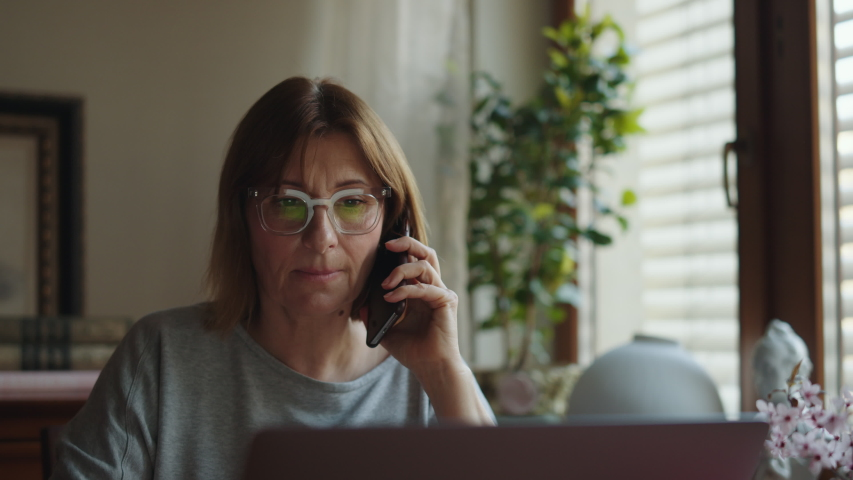 Portrait of an adult tired woman talking on the phone and working on a laptop. Mature woman freelancer speaks on a smartphone at a computer and looks at the monitor. Remote work freelancer at home Royalty-Free Stock Footage #1054702658