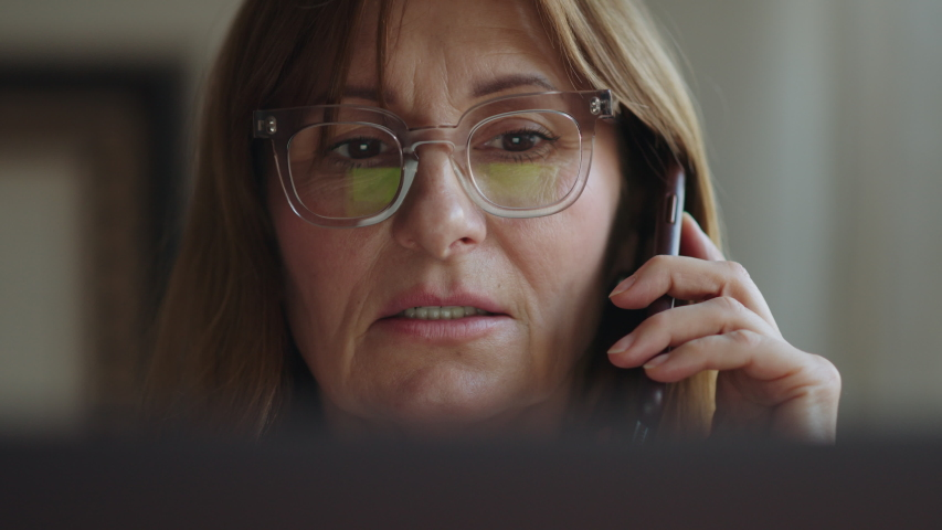 Mature woman freelancer speaks on a smartphone at a computer and looks at the monitor. Portrait of an adult tired woman talking on the phone and working on a laptop. Remote work freelancer at home Royalty-Free Stock Footage #1054702694