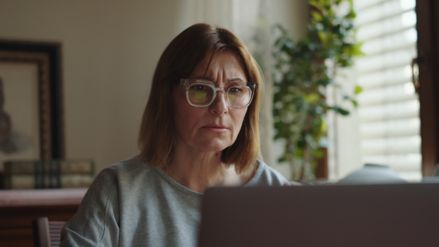 Portrait of an adult rastroinoy woman working at a laptop. Tired Mature woman freelancer at the computer looking at the monitor. Remote work freelancer at home workplace. | Shutterstock HD Video #1054702697