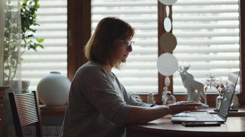Portrait of an adult woman working on a laptop. Mature woman freelancer at a computer looking at the monitor. Remote work freelancer at home workplace. Royalty-Free Stock Footage #1054702745