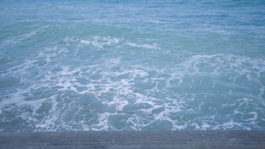 The waves on the coast, the view from the top. Close up. Blue tint.