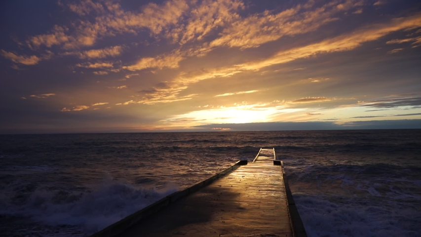 Concrete pier that goes out to sea against the background of the sunset. The concept of marine recreation. The sun sets in the sea. Waves crash against the pier. | Shutterstock HD Video #1054703228
