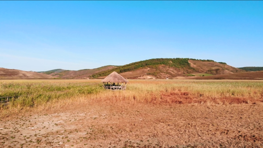 Low flight flyby wooden rural thatched roof hut in green grassy field towards brown sloping hill in background, overhead aerial approach   Shutterstock HD Video #1054703360