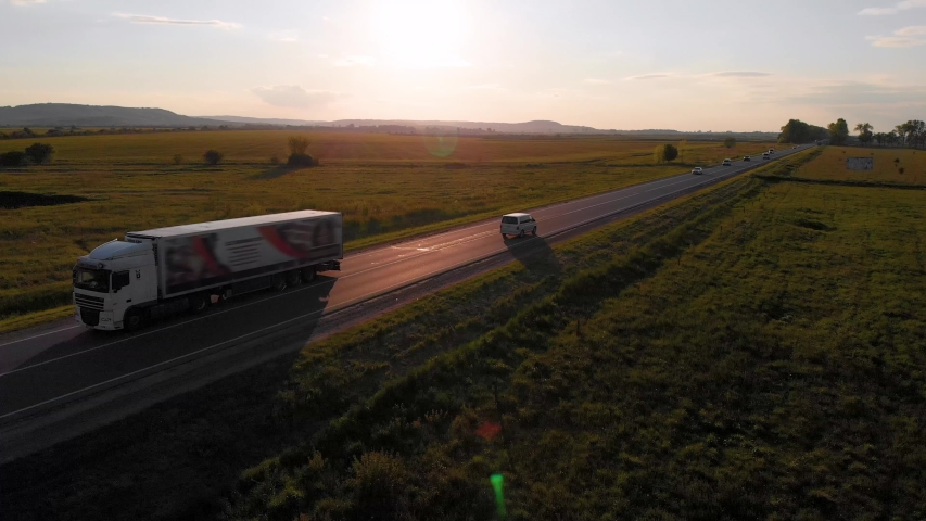 Aerial shot: vehicles, trucks and cars driving by road. Sunset summer time. 4K   Shutterstock HD Video #1054703459