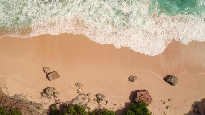 Top down aerial view from above of giant ocean waves crashing and foaming on empty sand tropical beach with big rock stones. Bird's eye aerial shot of golden beach meeting deep blue ocean water.