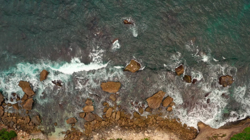 Aerial top view of waves break on rocks in a blue ocean. Sea waves on beautiful beach aerial view drone 4k shot. Bird's eye view of ocean waves crashing against an empty stone rock cliff from above.   Shutterstock HD Video #1054704014