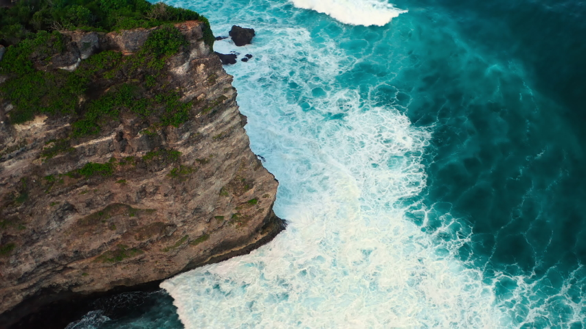 Aerial top view of waves break on rocks in a blue ocean. Sea waves on beautiful beach aerial view drone 4k shot. Bird's eye view of ocean waves crashing against an empty stone rock cliff from above. Royalty-Free Stock Footage #1054704035