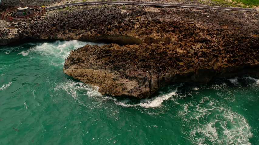 Aerial top view of waves break on rocks in a blue ocean. Sea waves on beautiful beach aerial view drone 4k shot. Bird's eye view of ocean waves crashing against an empty stone rock cliff from above.   Shutterstock HD Video #1054704053