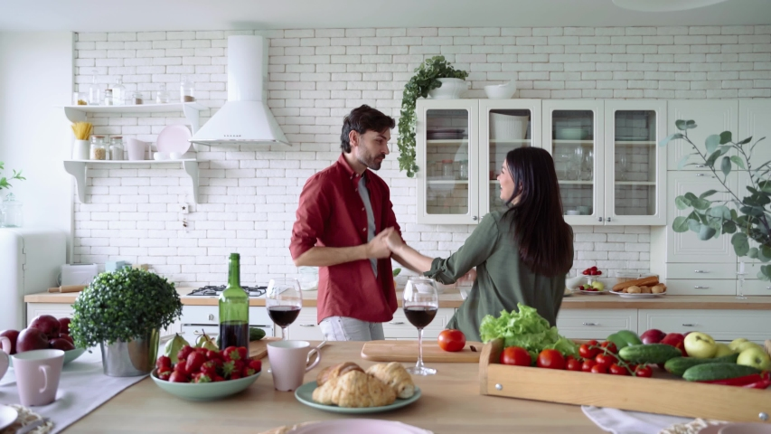 Romantic dinner. Happy joyful family couple drinking wine, dancing and having fun while preparing food together in the modern kitchen at home | Shutterstock HD Video #1054704311