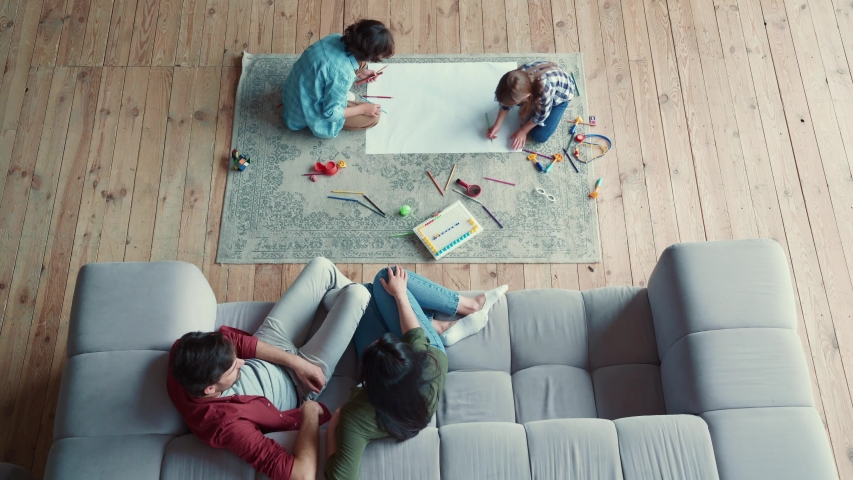 Creative activity. Top view of two little kids, brother and sister drawing with pencils, lying on the floor while young parents relaxing on the sofa | Shutterstock HD Video #1054704320