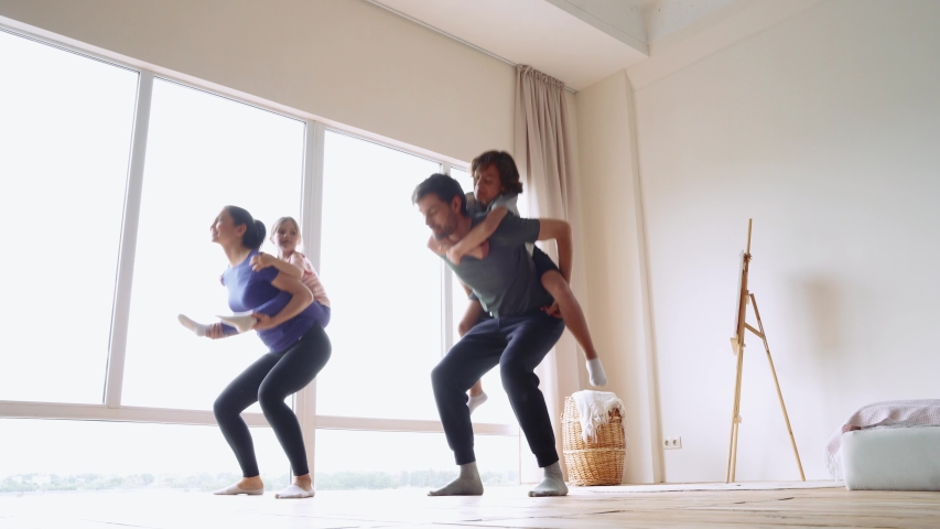 Sporty family doing sport together at home. Young beautiful parents carrying two little excited kids on back and doing squats in the bright modern room at home Royalty-Free Stock Footage #1054704323