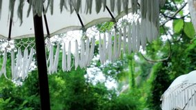 Video of an old white decorated fabric umbrella from the sun standing in the forest