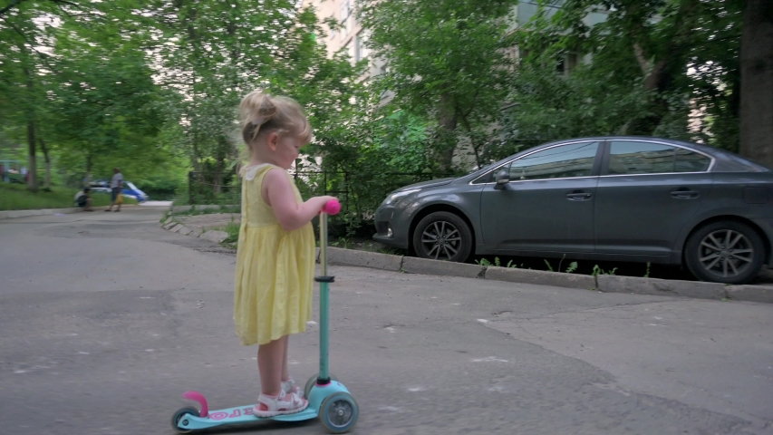 Little cute caucasian girl in yellow dress riding a scooter without helmet really fast | Shutterstock HD Video #1054705286