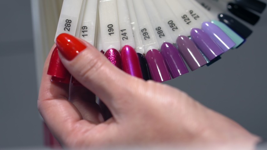 Woman chooses nail polish color for her nails manicure | Shutterstock HD Video #1054706528
