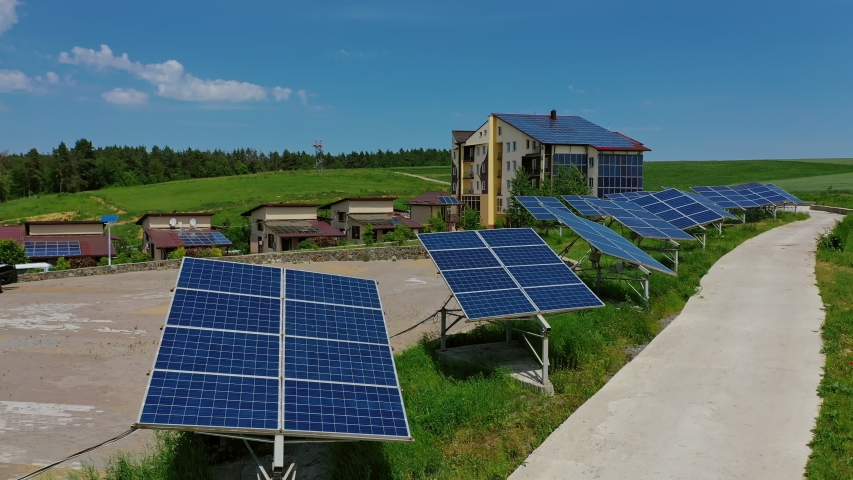 Solar panels on green field. Modern solar power plant on the roof of the house. Solar panels generate electricity. Solar power station generates alternative energy. | Shutterstock HD Video #1054706846