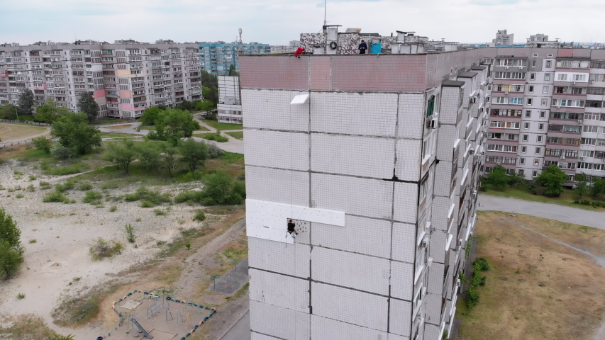 Aerial View on Industrial Climber Suspended on Ropes Performs Work on Insulation Facade of High-rise Building using Styrofoam. Industrial alpinism. Drone view on side multi-story residential building | Shutterstock HD Video #1054707002