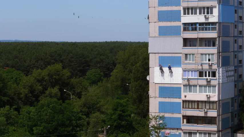 Industrial Alpinism. Two Climbers Suspended on Ropes Performs Work on the Insulation of the Facade of High-rise Building using styrofoam. Warms an old panel multi-story residential building using Foam