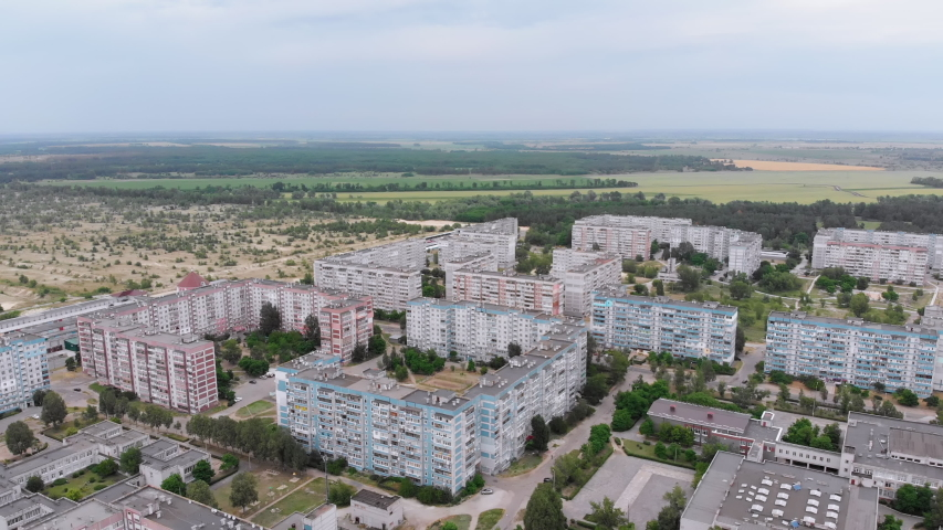 Aerial Panorama on Dwelling Blocks with Multistory Colorful Buildings near Nature and River. USSR apartments in housing condominiums for families. Panorama to rooftops and facades. Fly over small town | Shutterstock HD Video #1054707050