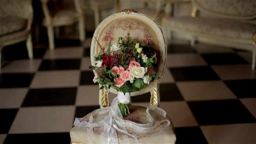 A beautiful bouquet of flowers stands on a beautiful chair. Close up. The camera is in motion | Shutterstock HD Video #1054707266