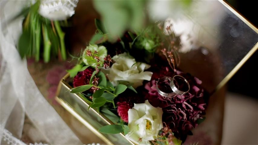 Beautiful wedding rings lie among the flowers. Beautiful reflections. Close up | Shutterstock HD Video #1054707278