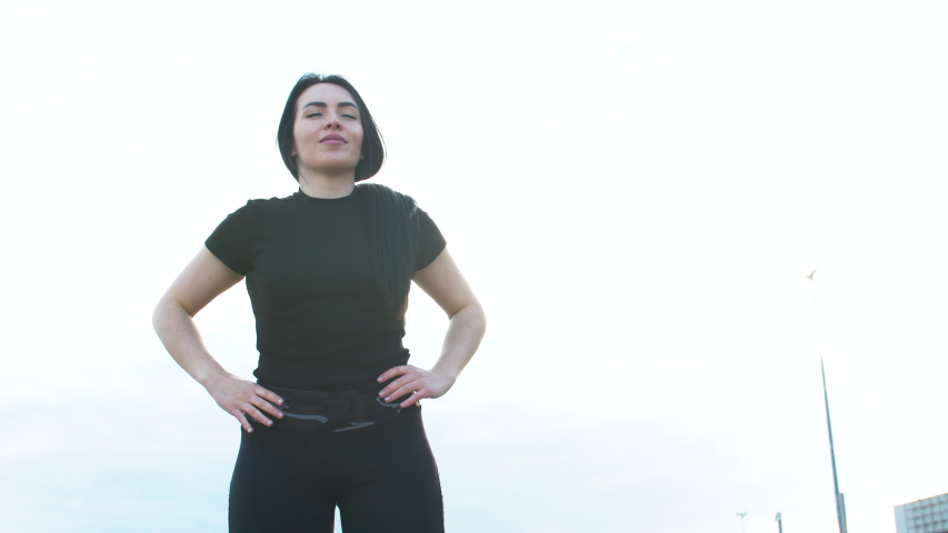 Young athletic woman doing breathing exercises outdoors. A woman in black sportswear doing Pilates. Warm-up before training   Shutterstock HD Video #1054707980