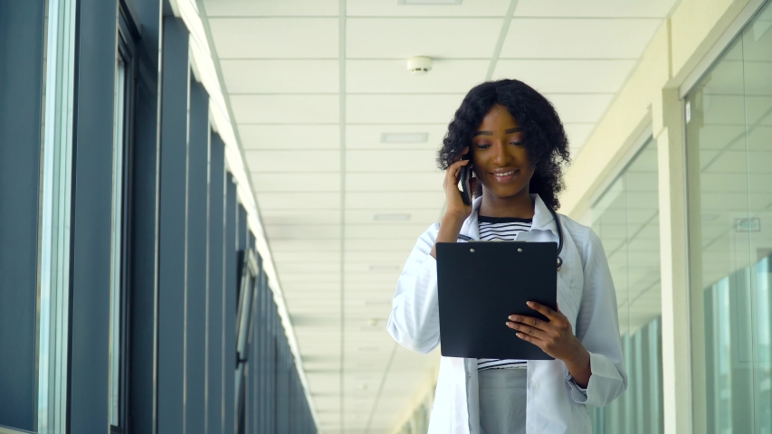 Smiling african american nurse talking on the phone with a notebook in a corridor of a modern hospital. Concept of medicine, health care and people