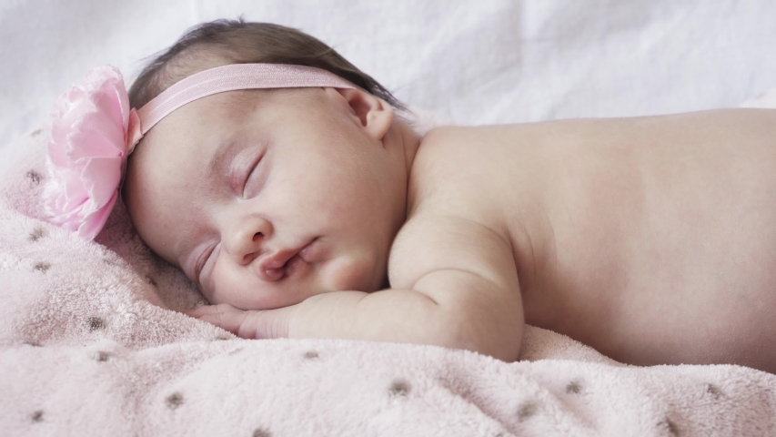 Infancy, childhood, development, medicine and health concept - close-up face of a newborn naked sleeping baby girl lying on her stomach with a bandage and a flower on her head on a pink background.
