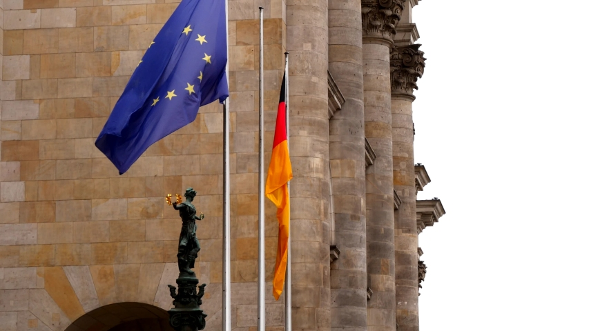 Flags of Germany and the European Union on the facade of the Reichstag building (Deutscher Bundestag). Fabric flags flutter in the wind on a cloudy day. | Shutterstock HD Video #1054709909
