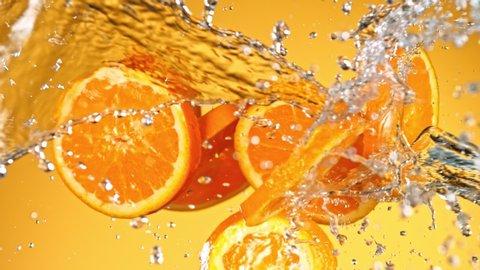 Super Slow Motion Shot of Flying Fresh Orange Slices and Water Side Splash on Orange Background at 1000fps.