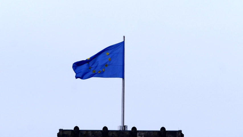 Flags of the European Union on the roof of the Reichstag building (Deutscher Bundestag). Fabric flags flutter in the wind on a cloudy day.  | Shutterstock HD Video #1054710554