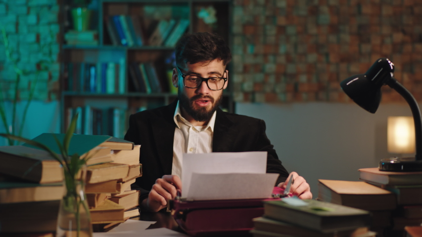 Good looking guy doing his project from the college he typing on the typewriter in the library very concentrated. 4k Royalty-Free Stock Footage #1054710578