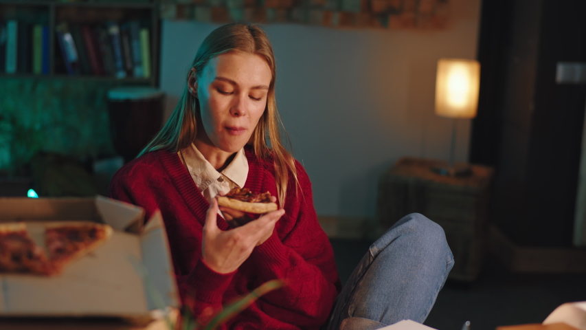In the library attractive lady student eating some pizza after she end the college project she are happy and excited | Shutterstock HD Video #1054710587