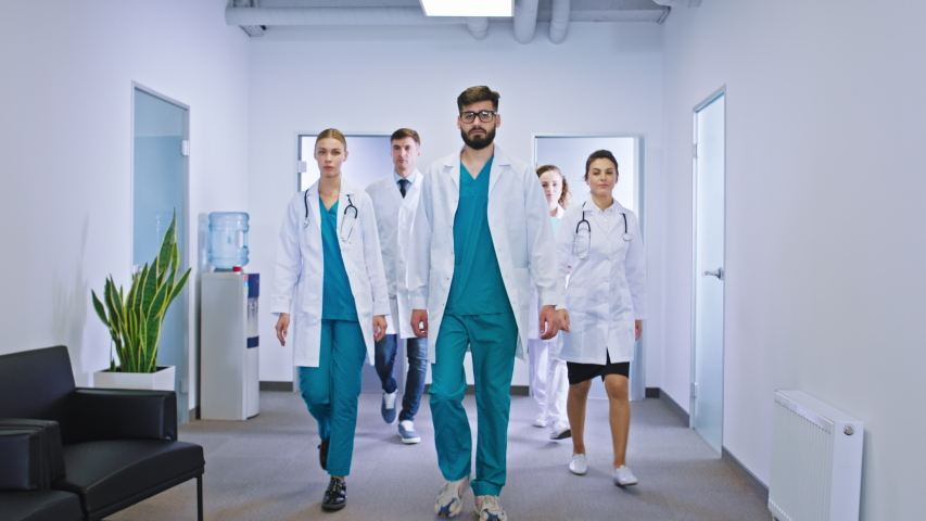 In a large hospital modern corridor walking in front of the camera group of do and nurses they stop and looking to the camera