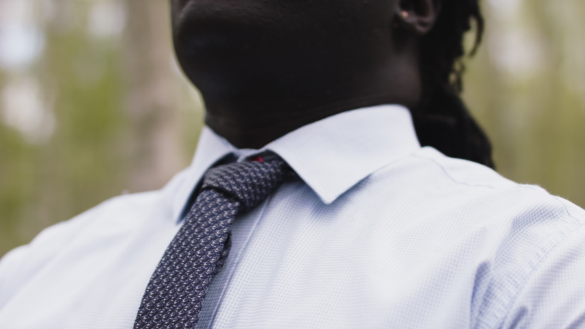 African businessman adjusting necktie in the nature. Close up slow motion shot. | Shutterstock HD Video #1054712039