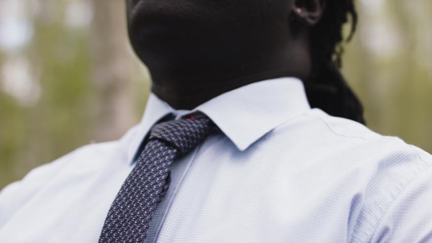 African businessman adjusting necktie in the nature. Close up slow motion shot.