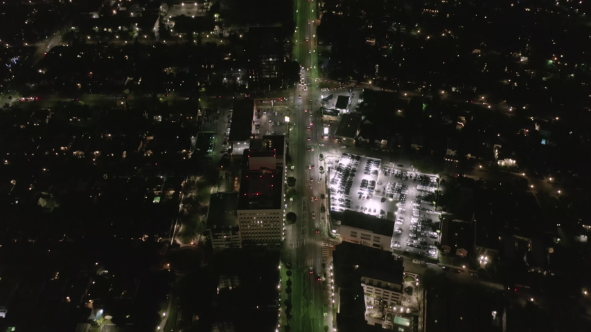 AERIAL: Lookup over Wilshire Boulevard Street in Hollywood Los Angeles at Night with View on Downtown and Glowing Streets and City Car Traffic Lights