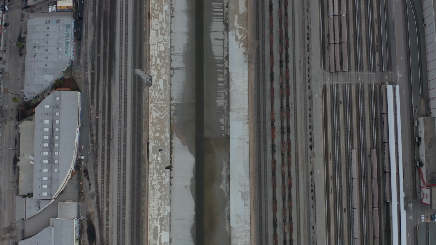 AERIAL: Overhead , Birds Eye View on Los Angeles River with Water on Cloudy Overcast Sky next to Train Tracks  | Shutterstock HD Video #1054712312