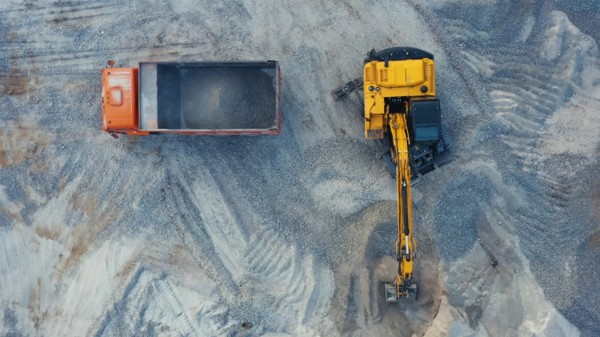 Aerial top down view of an excavator loading crushed stone into a dump truck in a crushed stone quarry Royalty-Free Stock Footage #1054712504