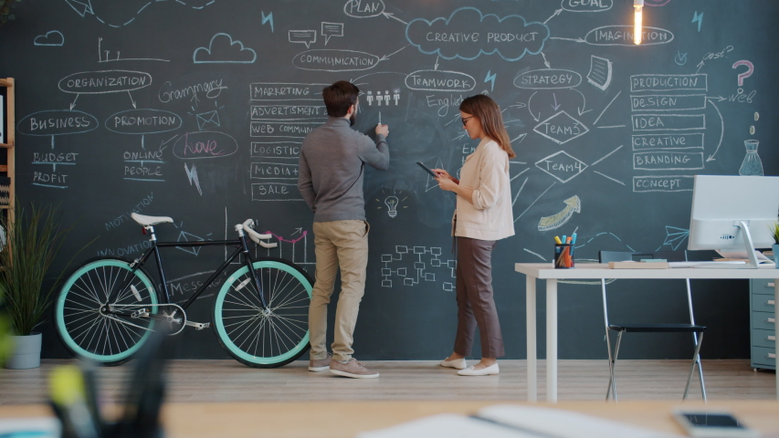 Man and woman coworkers are writing on chalk board discussing business strategy in open space office. Interior, coworking space and marketing concept. | Shutterstock HD Video #1054712591