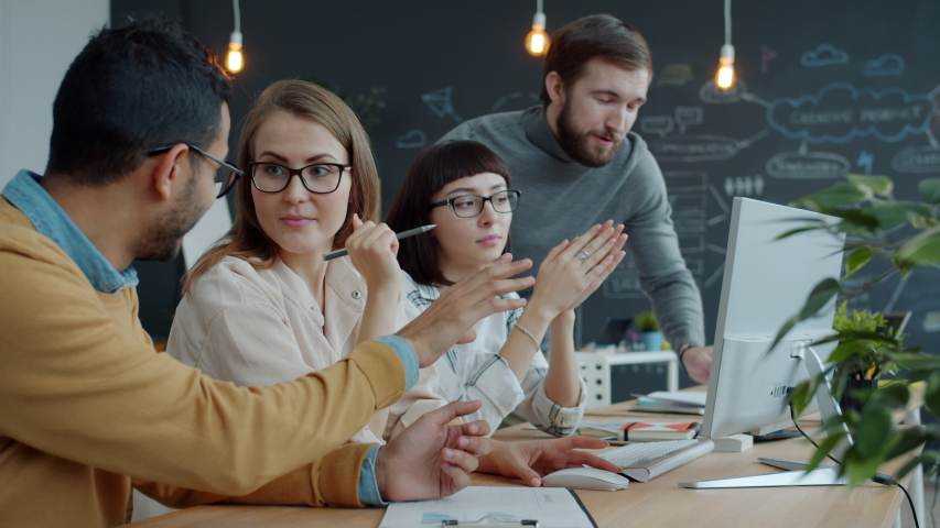 Slow motion of young men and women brainstorming speaking about business in shared office sharing ideas. Communication and businesspeople concept. Royalty-Free Stock Footage #1054712600