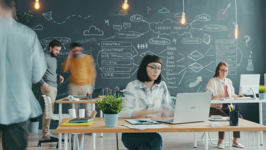 Zoom-in time lapse of young woman working in open space office with people moving around, coworkers are busy with work. Workspace and business concept.