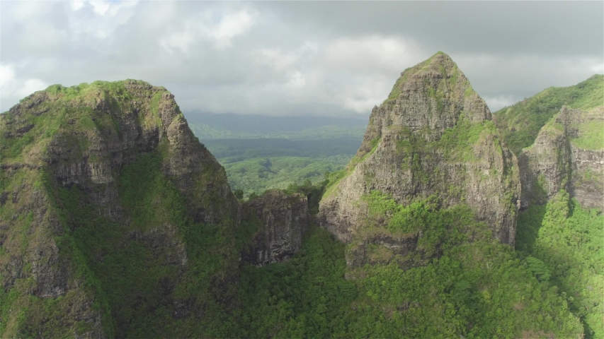 Aerial flying between majestic mountain tops above lush rainforest jungle