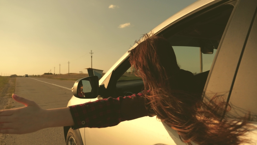 Girl traveler with long hair travels, sits in front seat of car, stretches his hand out of window and catches glare of sun. Free woman rides a car, catches wind with her hand from car window.