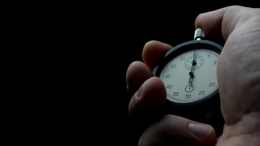 Analogue stopwatch in hand on the black background time start with old chronometer man presses start button in the sport concept | Shutterstock HD Video #1054713224