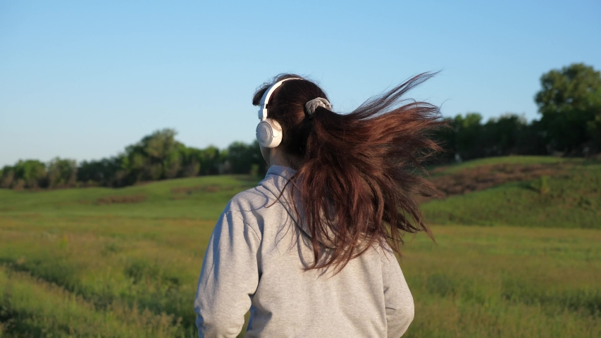 Healthy beautiful girl is engaged in fitness, jogging in country. training jogging. Free young woman runs in summer in park at dawn listens to music with headphones. Jogger girl breathes fresh air